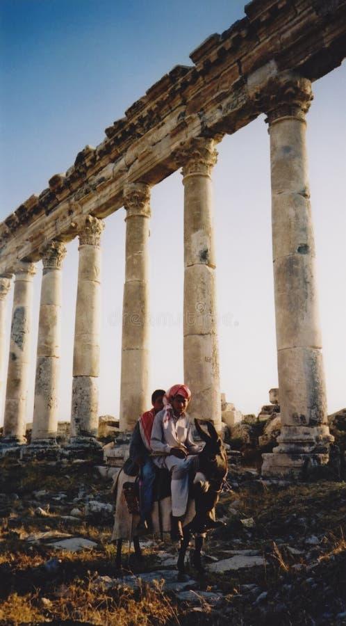 Muchachos árabes en las ruinas romanas del burro fotos de archivo