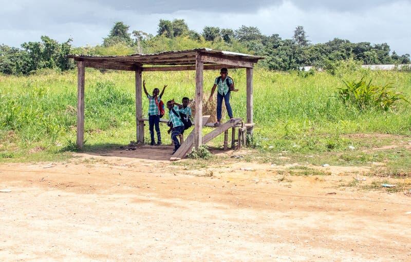Muchachos alegres en una parada de autobús fotografía de archivo libre de regalías