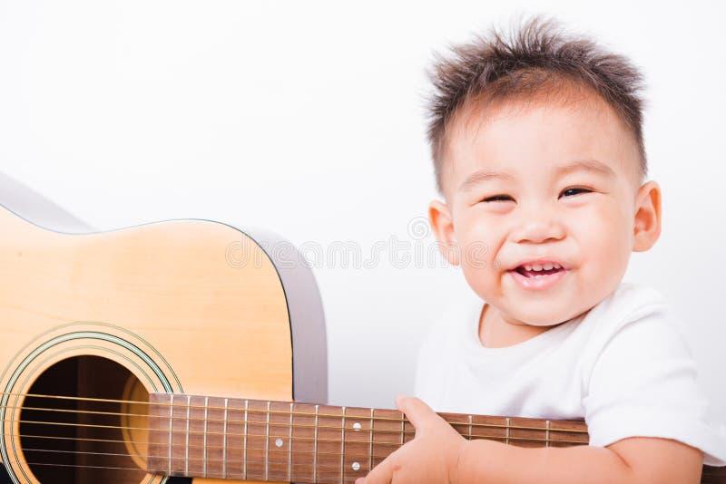 Muchachos asi?ticos del ni?o del retrato 1 a?o 6 meses que tocan la guitarra fotos de archivo libres de regalías