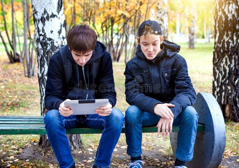Muchachos con una tableta al aire libre imagenes de archivo