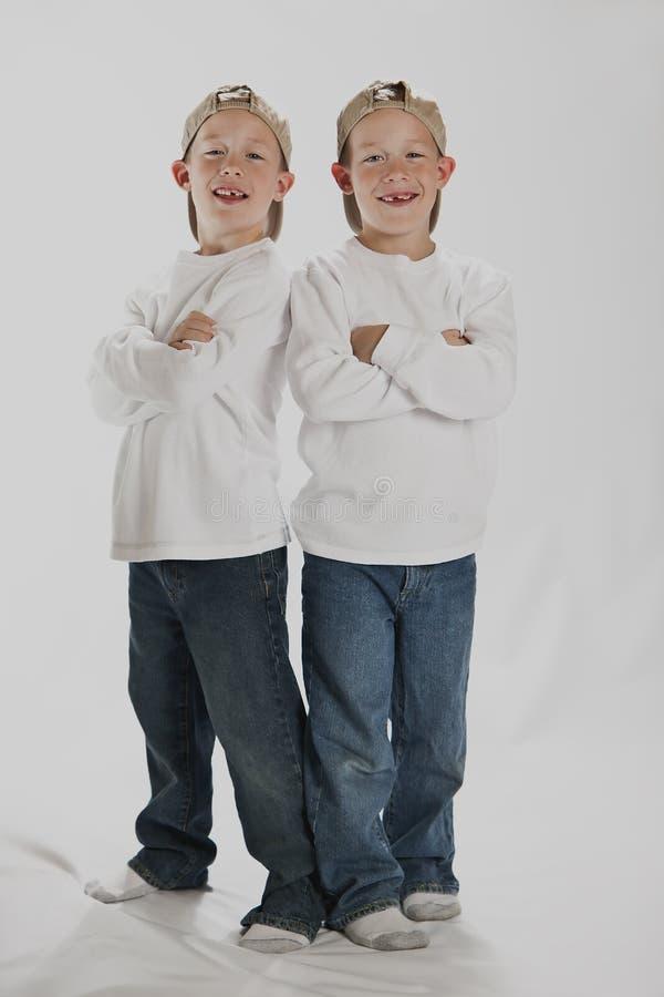 Muchachos de 6 años, gemelos que desgastan los sombreros de un béisbol fotografía de archivo libre de regalías