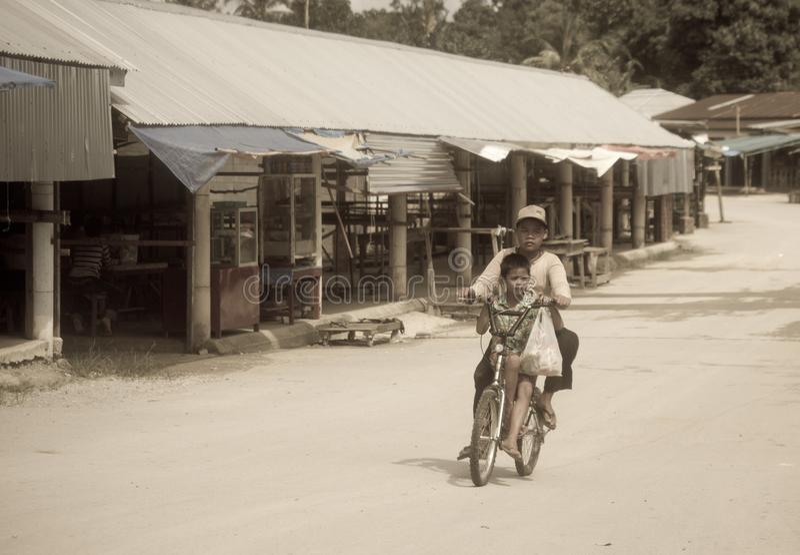 Muchachos de la pobreza que montan en una bicicleta a lo largo de una calle vacía imágenes de archivo libres de regalías