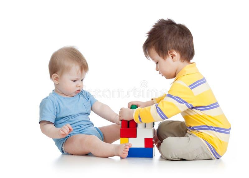 Muchachos de los niños que juegan con los juguetes junto Aislado en el fondo blanco fotos de archivo