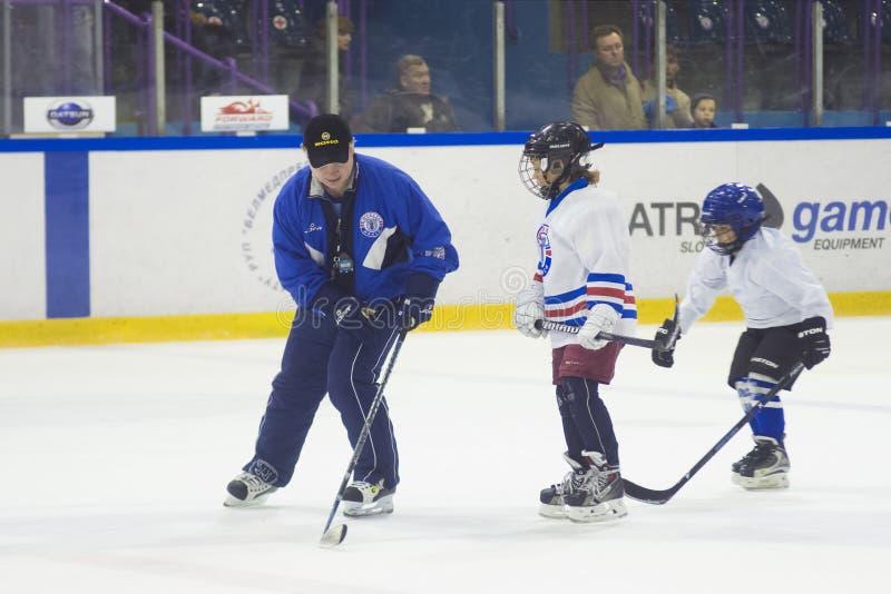 Muchachos de los niños que juegan a hockey en el hielo en el estadio de Yunost imagenes de archivo