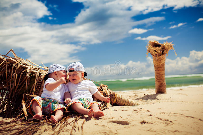 Muchachos del gemelo idéntico que se relajan en una playa imagen de archivo libre de regalías