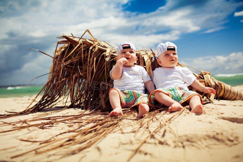 Muchachos del gemelo idéntico que se relajan en una playa imagenes de archivo