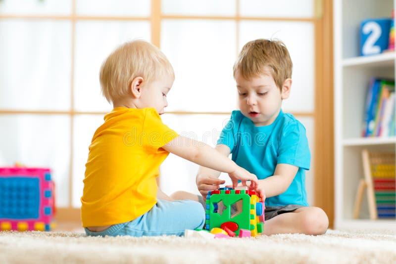 Muchachos del preescolar del niño de los niños que juegan el juguete lógico que aprende formas y colores en casa o cuarto de niño imagen de archivo libre de regalías