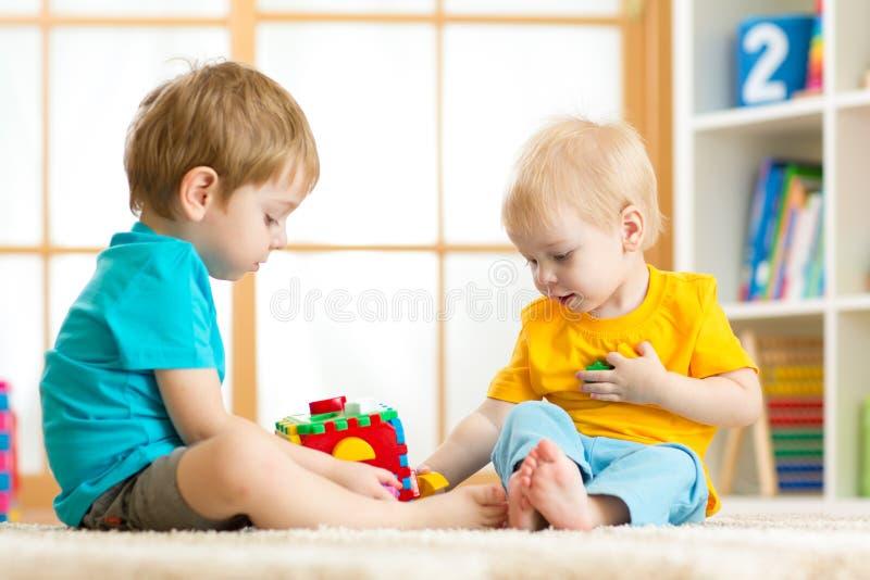 Muchachos del preescolar del niño de los niños que juegan el juguete lógico que aprende formas y colores en casa o cuarto de niño imágenes de archivo libres de regalías