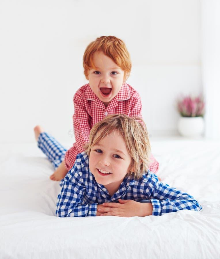 Muchachos felices, hermanos que juegan en el dormitorio en pijamas imagen de archivo libre de regalías