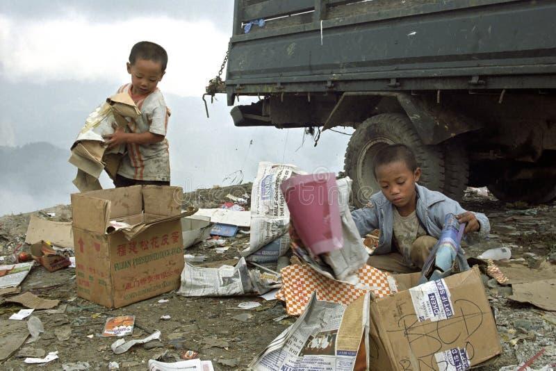 Muchachos filipinos pobres que recolectan el documento viejo sobre el vertido foto de archivo
