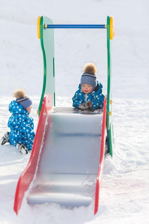 Muchachos gemelos que caminan en el parque en el invierno y el rollo con la armadura del hierro foto de archivo