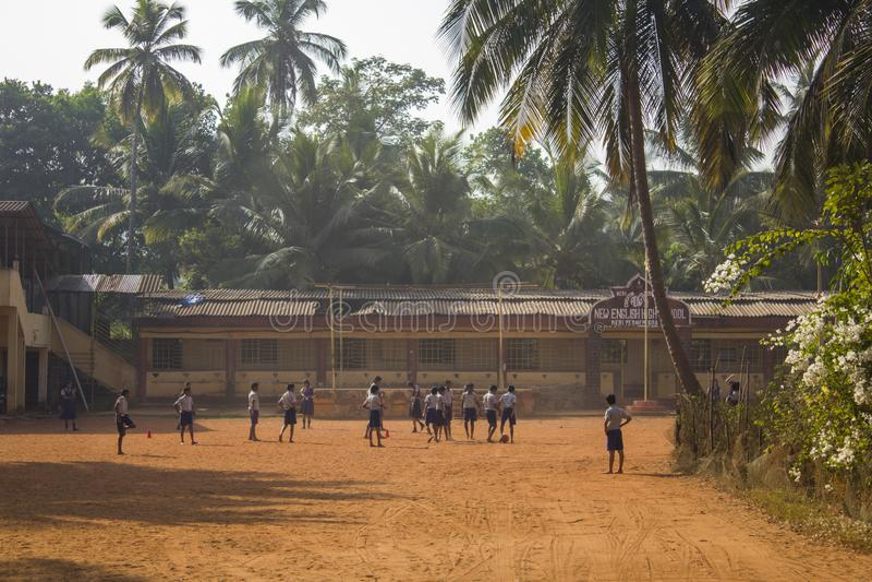 Muchachos indios y muchachas de los alumnos que juegan a fútbol descalzo en el patio de escuela debajo de la palma verde foto de archivo