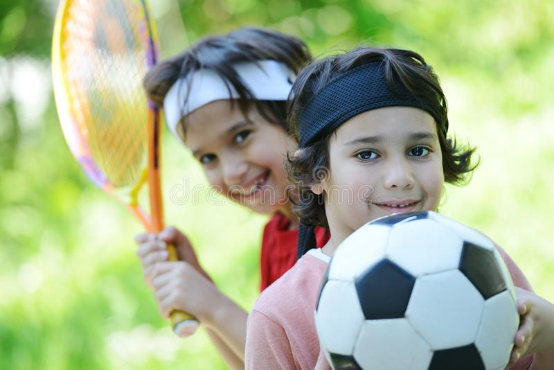 Muchachos jovenes con fútbol y tenis fotografía de archivo libre de regalías