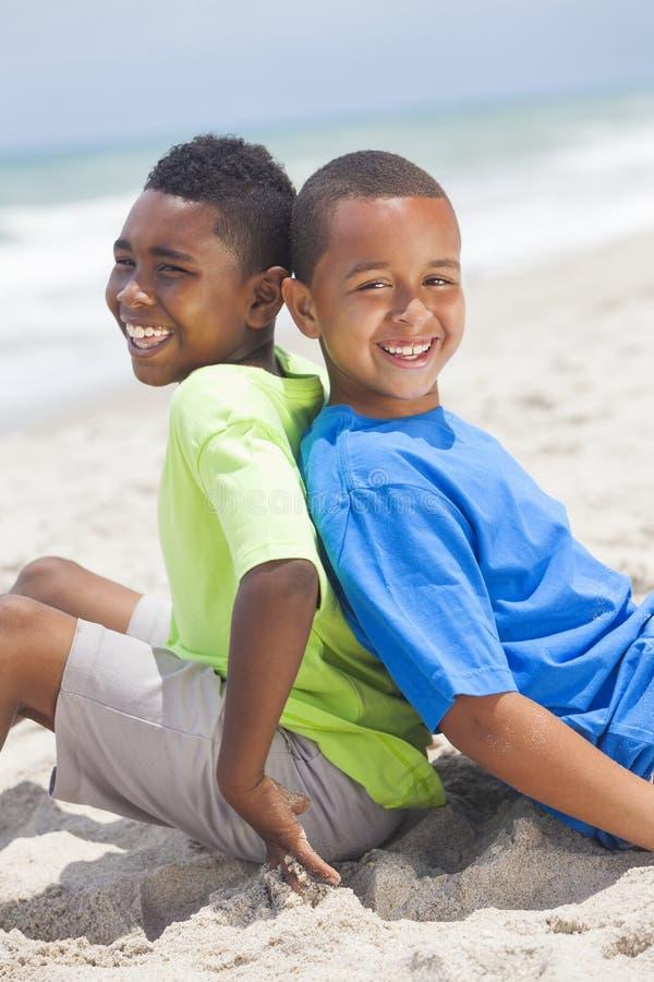 Muchachos jovenes del afroamericano que se sientan en la playa foto de archivo