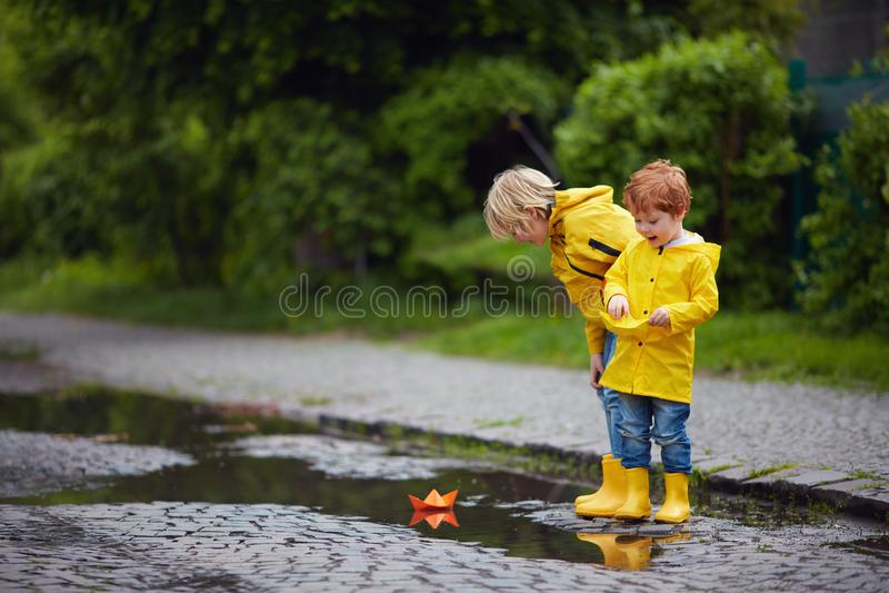 Muchachos jovenes felices, amigos que juegan en charcos de la primavera con los barcos de papel coloridos imágenes de archivo libres de regalías