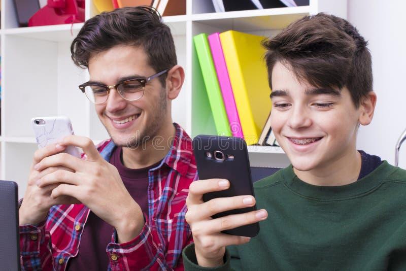 Muchachos jovenes que miran los teléfonos móviles fotografía de archivo libre de regalías
