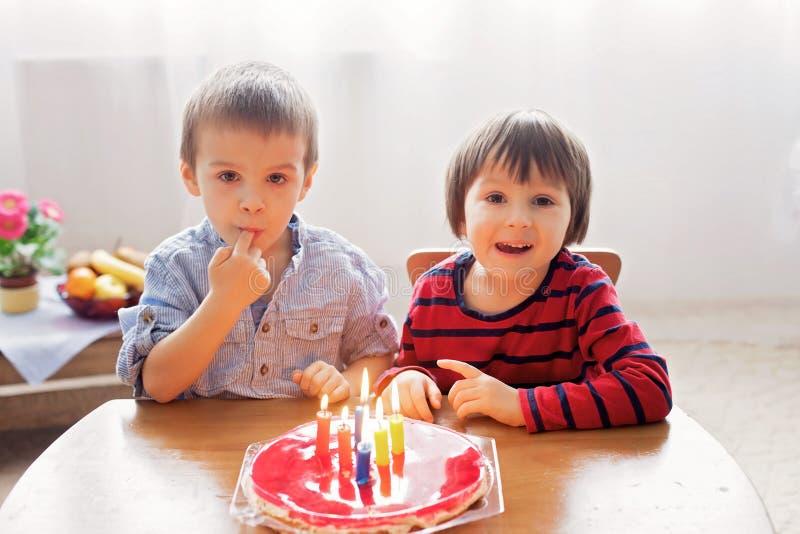 Muchachos lindos adorables, velas que soplan en una torta de cumpleaños fotos de archivo