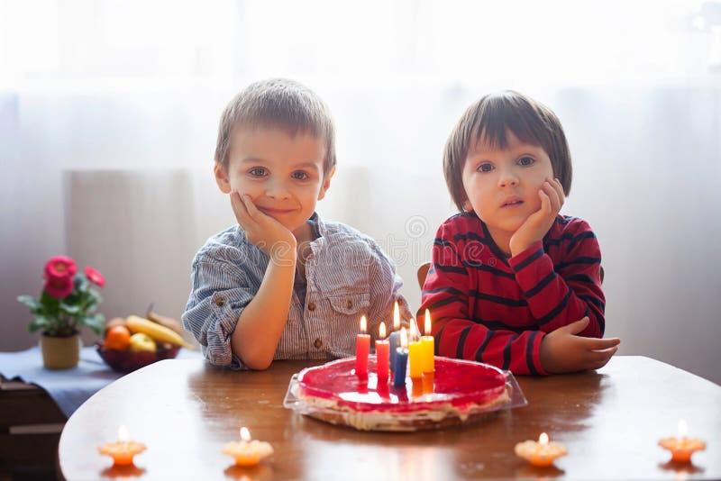 Muchachos lindos adorables, velas que soplan en una torta de cumpleaños foto de archivo