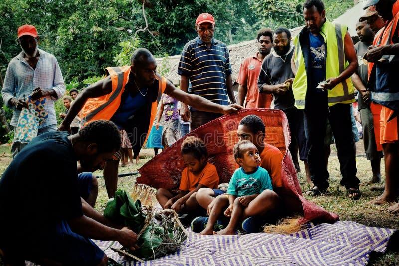 muchachos lindos que aceptan ofrendas como el taro, ñame, esteras tejidas tradicionales para su ritual de la circuncisión imagen de archivo