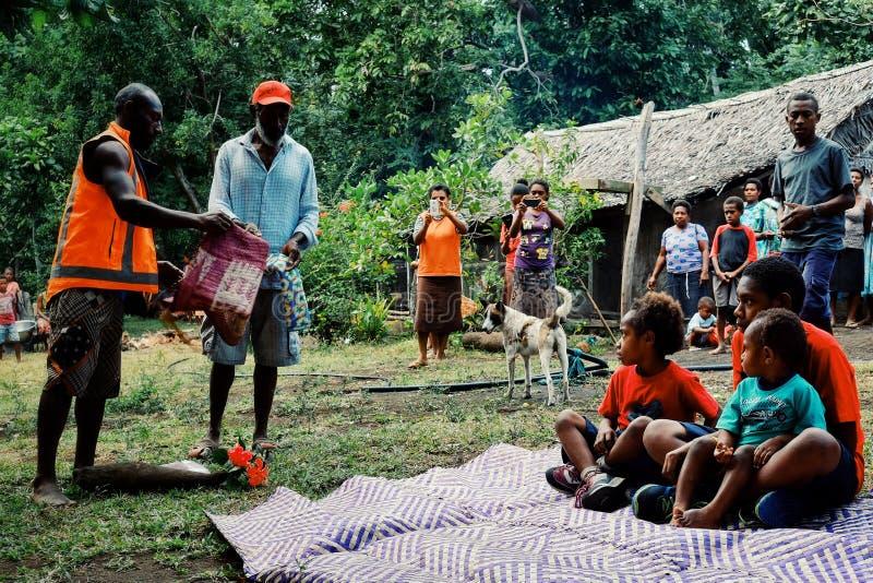 muchachos lindos que aceptan ofrendas como el taro, ñame, esteras tejidas tradicionales para su ritual de la circuncisión foto de archivo