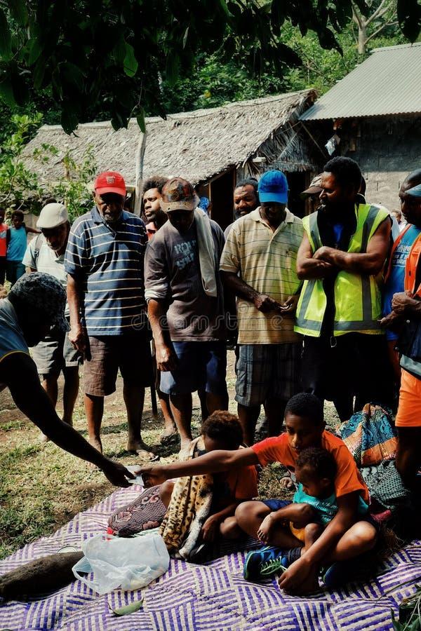 muchachos lindos que aceptan ofrendas como el taro, ñame, esteras tejidas tradicionales para su ritual de la circuncisión fotografía de archivo libre de regalías