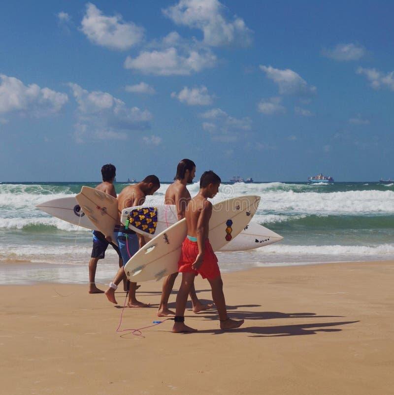 Muchachos no identificados que caminan con los tableros de resaca en la playa foto de archivo