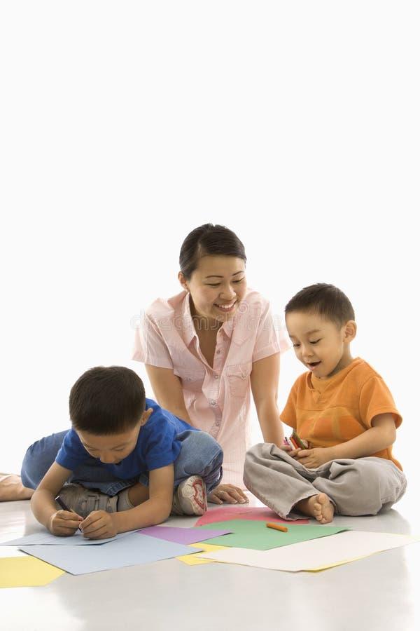 Muchachos que colorean con la madre. fotos de archivo