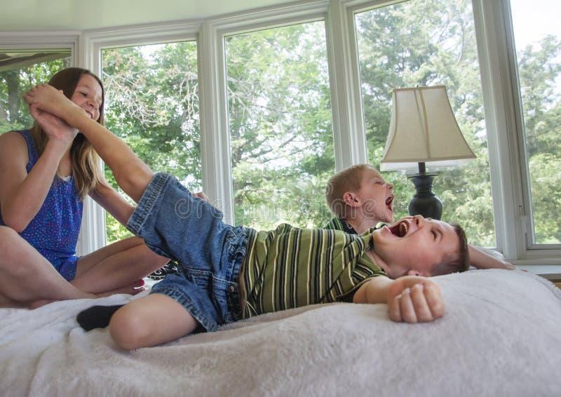 2 muchachos que consiguen pies cosquilleados imagenes de archivo