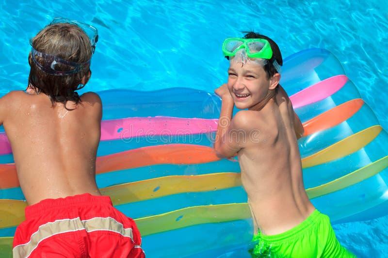 Muchachos que flotan en agua foto de archivo