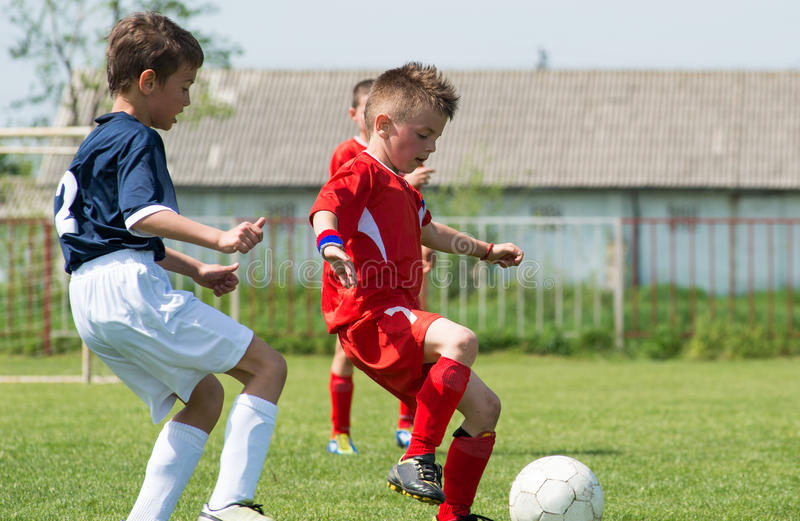 Muchachos que golpean fútbol con el pie fotos de archivo