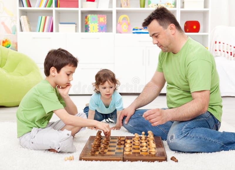 Muchachos que juegan a ajedrez con su padre fotografía de archivo libre de regalías