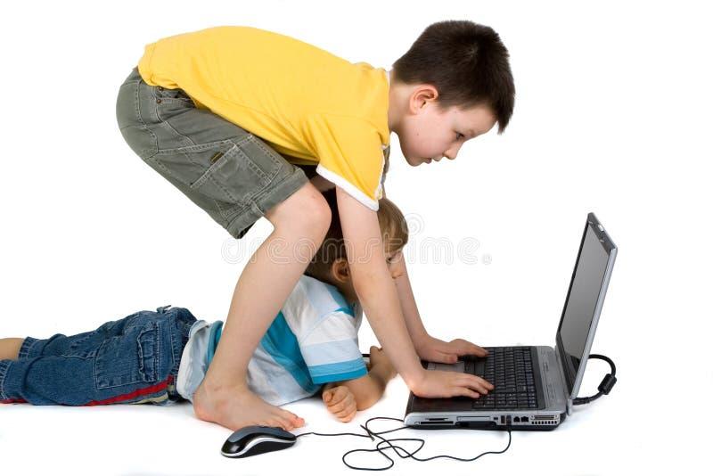 Muchachos que juegan con la computadora portátil imagen de archivo