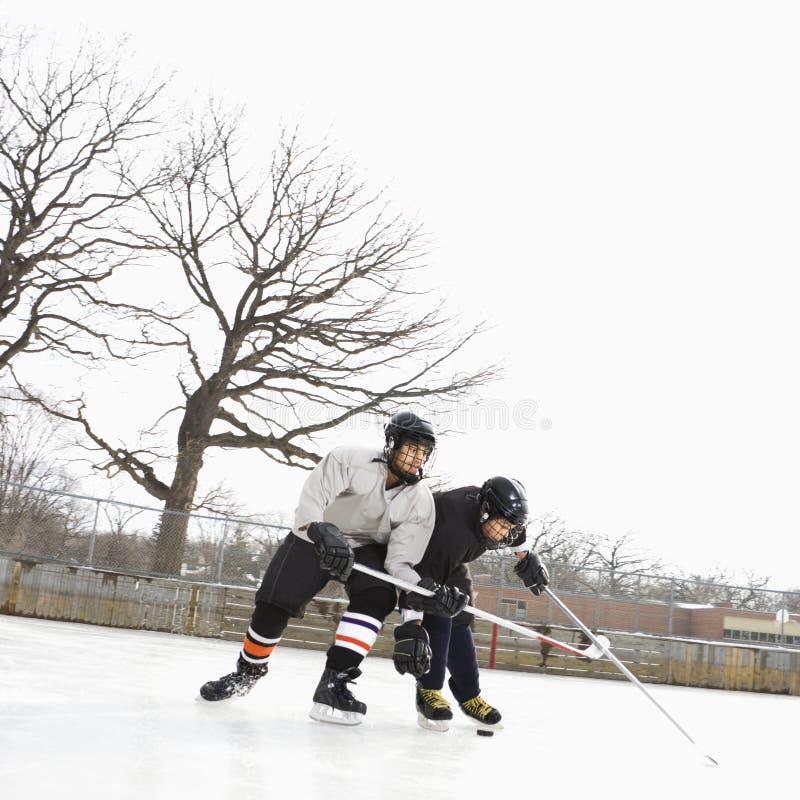 Muchachos que juegan deporte de invierno. imagen de archivo libre de regalías