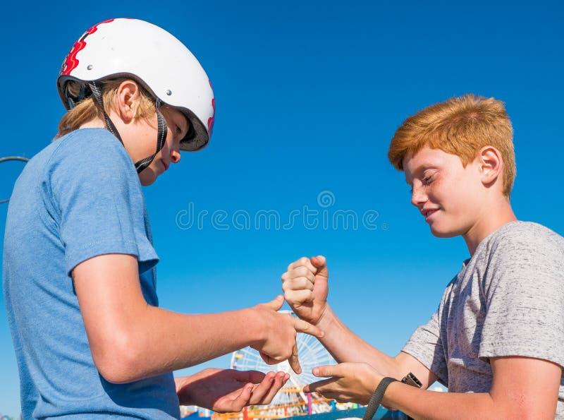 Muchachos que juegan el papel, roca, tijeras en Santa Monica Pier foto de archivo libre de regalías