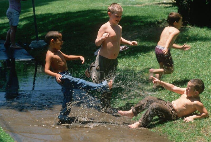 Muchachos que juegan en agua imagen de archivo