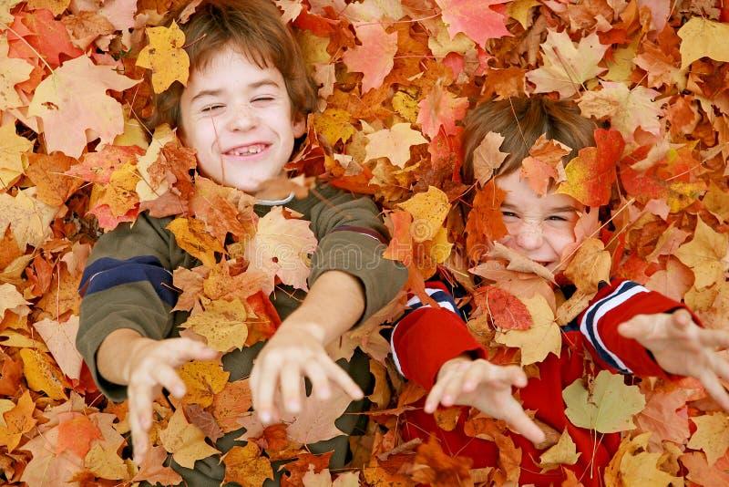 Muchachos que juegan en las hojas fotos de archivo libres de regalías
