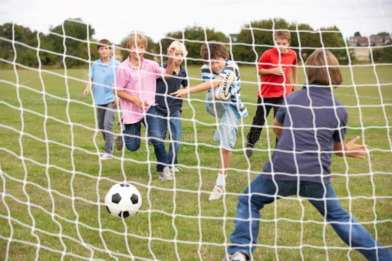 Muchachos que juegan a fútbol en parque fotografía de archivo libre de regalías