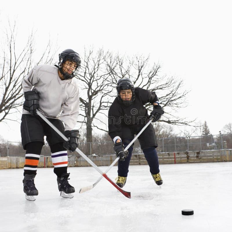 Muchachos que juegan a hockey sobre hielo. imagen de archivo