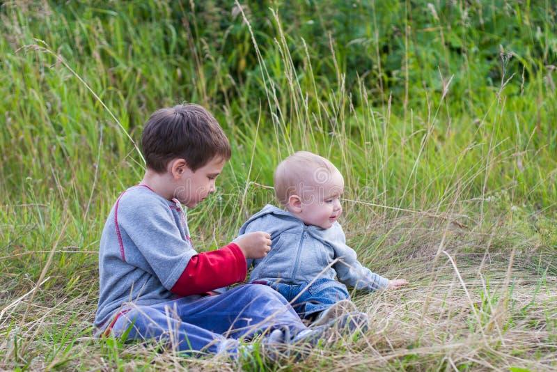 Muchachos que juegan junto en la hierba en el país imagen de archivo libre de regalías