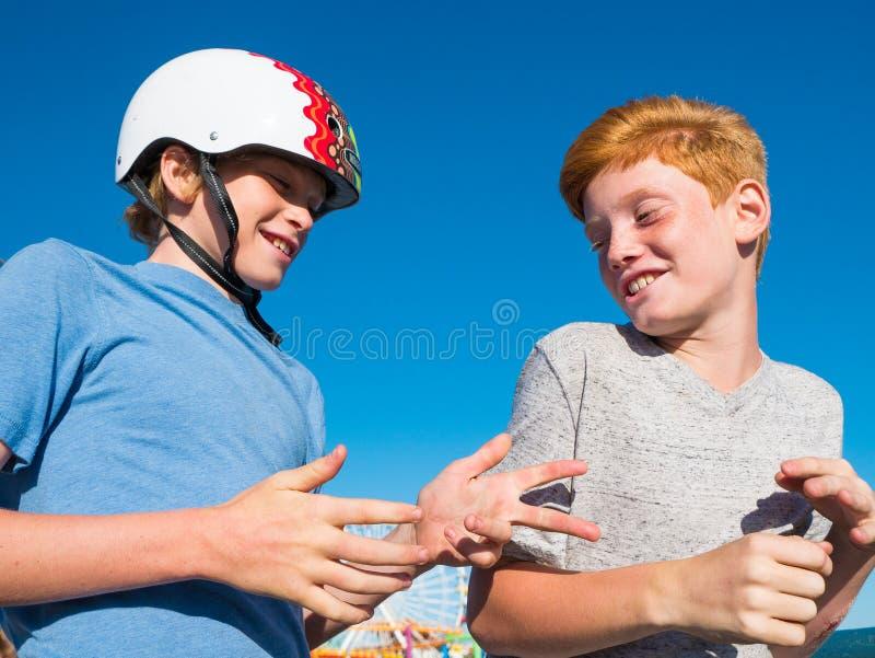 Muchachos que juegan la roca, papel, tijeras en Santa Monica Pier imagen de archivo