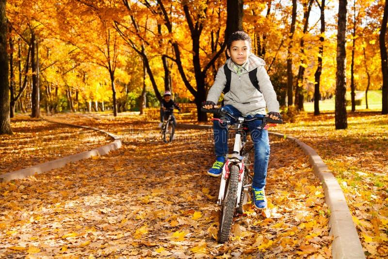 Muchachos que montan la bici en parque del otoño fotografía de archivo