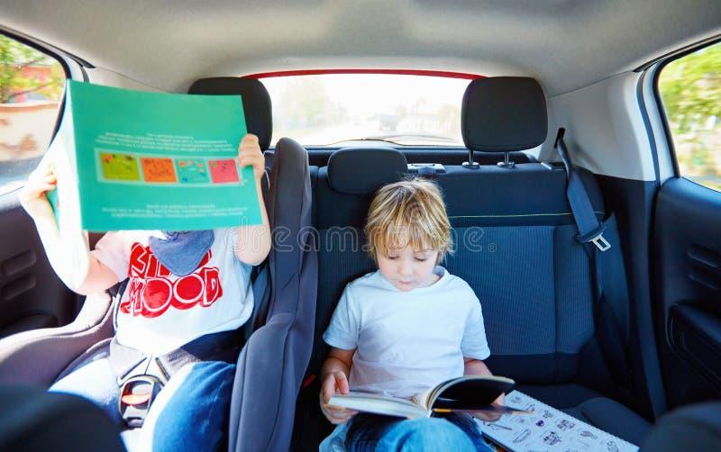Muchachos que se sientan en el asiento trasero, libro de lectura mientras que viaja en el coche fotos de archivo