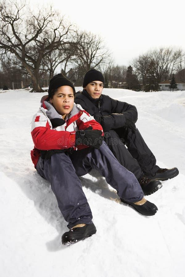 Muchachos que se sientan en nieve. imagen de archivo libre de regalías