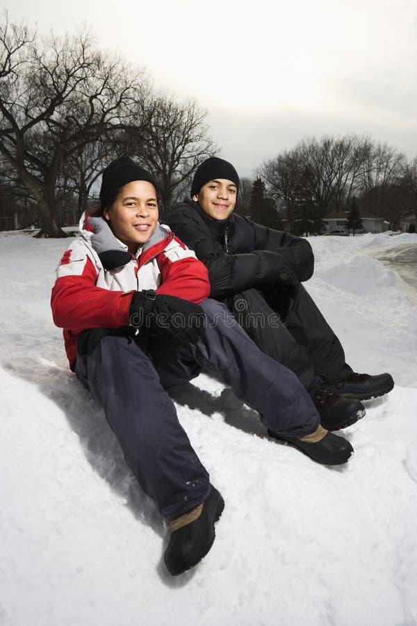 Muchachos que sonríen en nieve. imagenes de archivo