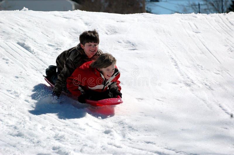 Muchachos sledding imagen de archivo