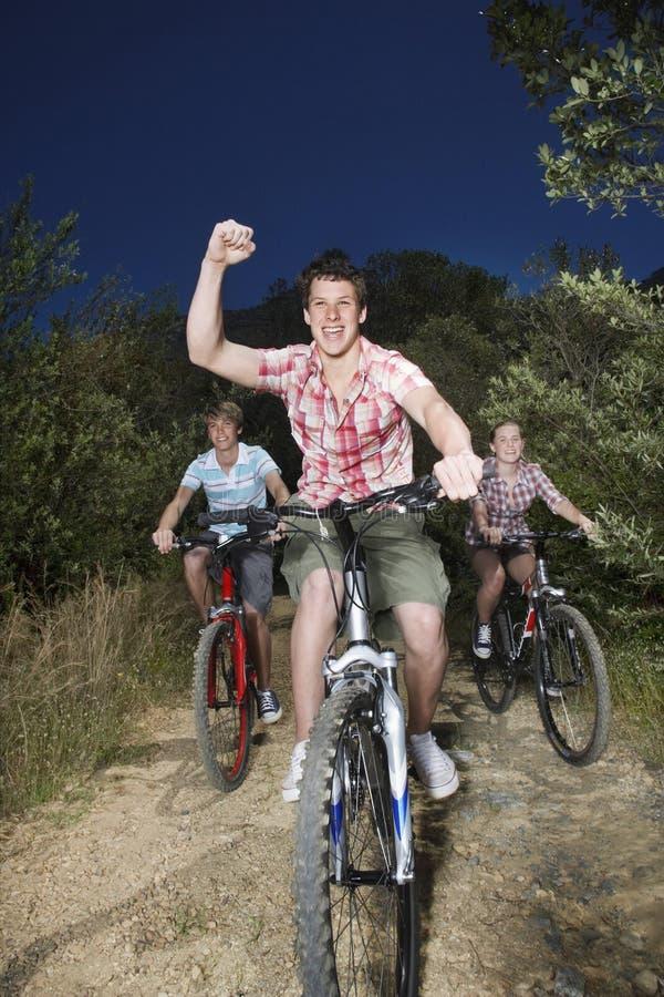 Muchachos y bicicletas del montar a caballo de la muchacha en la carretera nacional imagen de archivo libre de regalías
