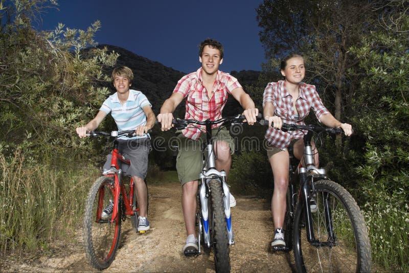 Muchachos y bicicletas del montar a caballo de la muchacha en la carretera nacional imagenes de archivo