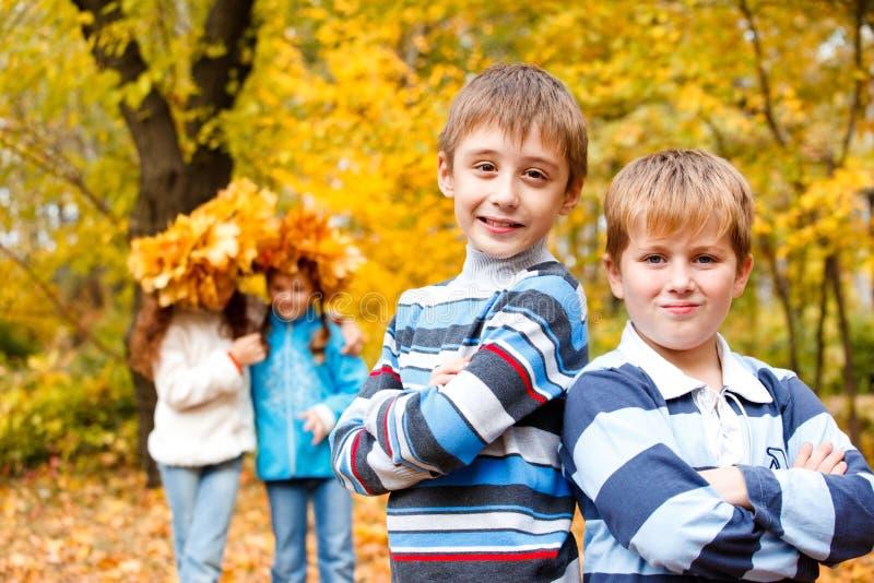 Muchachos y muchachas en parque del otoño fotografía de archivo libre de regalías