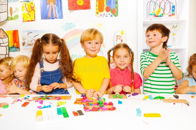 Muchachos y muchachas felices con plasticine en sala de clase fotografía de archivo libre de regalías