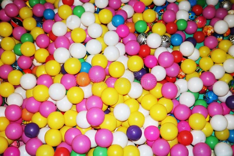 Muchas bolas plásticas coloridas en un ballpit de los niños en el patio imagen de archivo